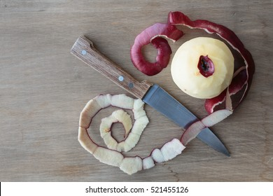 Peeling and apple with a knife.