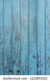 Peeling blue paint on decaying wood panel fence/door