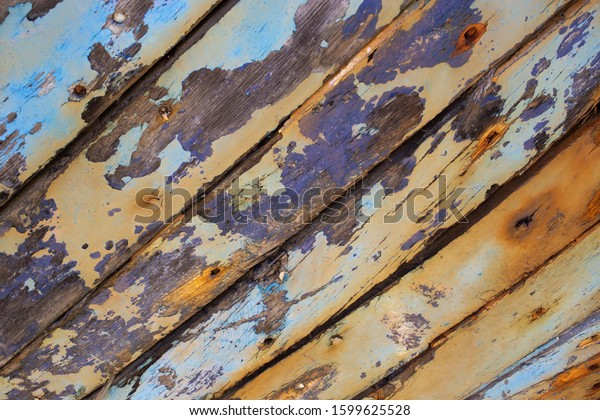 Peeling brown and blue paint over wooden background