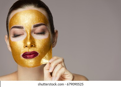 Peeling Cosmetic Gold Mask From Beautiful Face Skin.