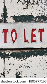 Peeling letters on a background of flaking paint say TO LET