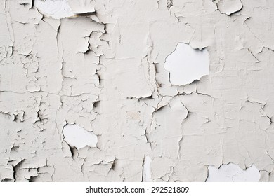 Peeling off white paint on a stone surface, as an abstract