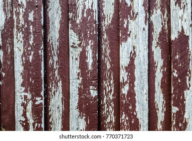 Peeling old red paint on timber wall background.