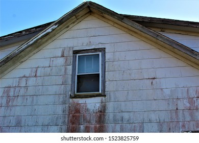 Peeling paint, bare wood, and an upstairs window contrast to the red mold on the side of this abandoned farmhouse.