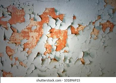 Peeling paint on concrete revealing an orange paint color underneath./ Aged, Cracked, Peeling Paint on Concrete