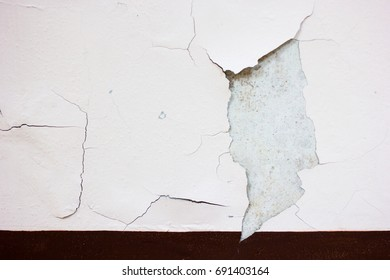 Peeling painted wall, texture, grunge background, cracked paint with dark brown skirting wall.