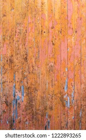 Peeling pink and orange paint on decaying wood panel fence/door