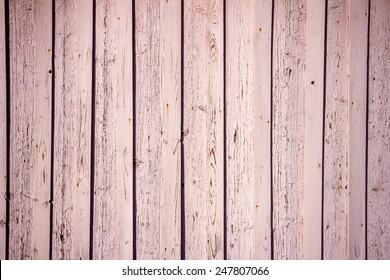 Peeling pink paint on weathered wood planks texture