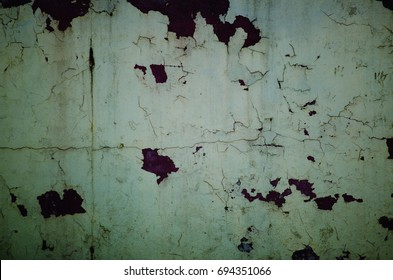 Peeling plaster on the wall in dark tones like in horror movies (as an abstract grungy background)
