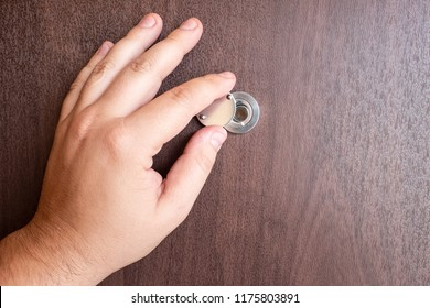 The Peephole And The Hand. Peep Hole Closeup. A Female Hand Opens The Cover