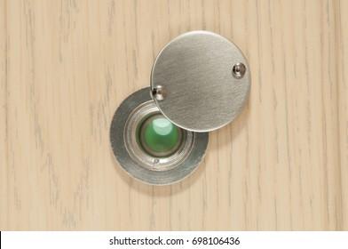 Peephole on wooden door close up