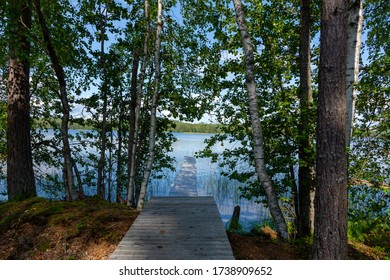 A peer on a lake in Finland seen through the forest