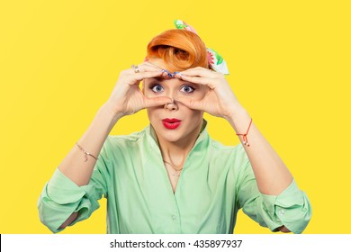Peering concept. Closeup portrait young pretty stunned curious woman peeking looking through fingers like binoculars searching for something looking to the future at camera isolated yellow background