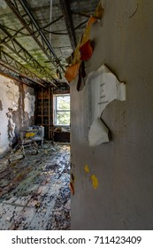 Peering through an open door of a view of a wet, deteriorated patient room inside an abandoned hospital.