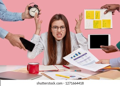 Peevish woman holds hands in disgust, being overwhelmed with much work, feels pressure from colleagues, sits at desktop with documentation, looks with annoyed expression, hides from difficulties