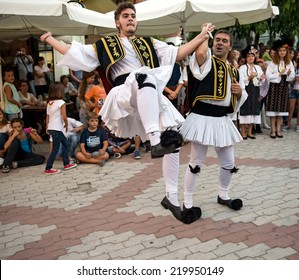 PEFKOHORI , GREECE - SEPTEMBER 19 2014 : Folk Dancers from several countries   dance in the Annual Folk Dance festival in the village square of Pefkohori ,Greece.The Greek dancers perform their dance.