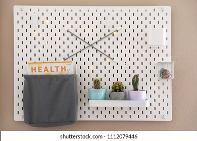 Pegboard with different cacti and magazine on wall