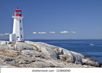 Peggy's Cove lighthouse, Nova Scotia, Canada.  Lobster boat gathering traps in the background.