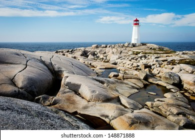 Peggy's Point Lighthouse in Nova Scotia Canada with blue sky and rocks in foreground