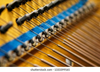 Pegs, damper and bass strings inside the old piano. The mechanism of musical instruments. Sound technology. Shallow depth of field. Closeup.