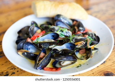 PEI (Prince Edward Island) Mussels topped with a house chorizo, herbs, spicy hollandaise with a grilled baguette.