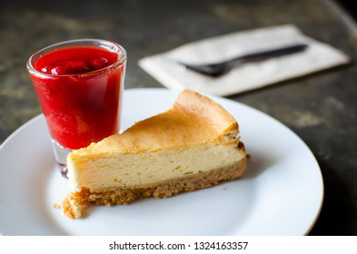 peice of cheese cake serve with strawberry syrup