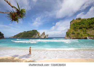 PEJUKUTAN, INDONESIA - JULY 9: An unidentified woman walks down Atuh beach in Pejukutan, Indonesia on July 9, 2017.