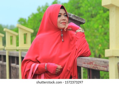 Pekalongan/Indonesia- february 10, 2018 : Asian Muslim women wearing red dresses standing by the pool