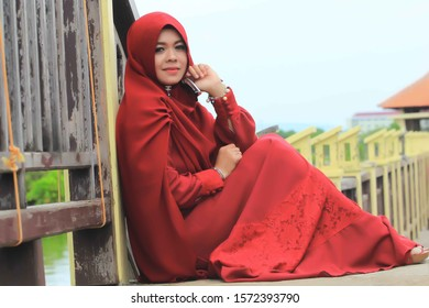 pekalongan/indonesia- feburary 10, 2018 : Asian Muslim women wearing red dresses standing by the pool