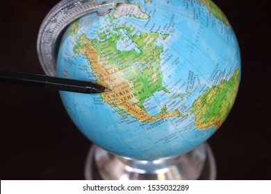 Pekalongan/Indonesia - October 17, 2019 :  Closeup shot of globe model with a map of the world over wooden table as background. selected focus
