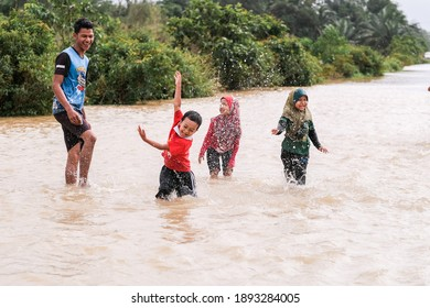 Pekan, Malaysia- January 12th, 2021 : A group of kids playing  on flood water at the road.