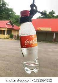 Pekan, Pahang, Malaysia : 4th May 2020 - Coca Cola bottle hanging on a rope is seen on a street in Pekan, Malaysia