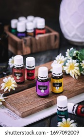 Pekanbaru, Indonesia - April 08 2020 ; Variety of Young Living Essential Oil. On the wooden board. Selective focus. Dark background.