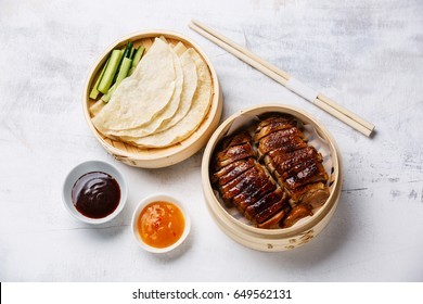 Peking Duck in bamboo steamer served with fresh cucumber, sauce and roasted wheaten chinese pancakes on white background