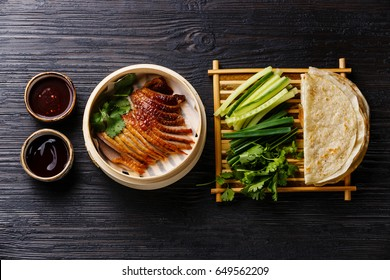 Peking Duck in bamboo steamer served with fresh cucumber, green onions, cilantro and roasted wheaten chinese pancakes with sauce Hoysin on black burned wooden background