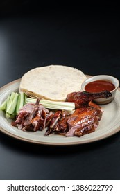 Peking duck on a plate on a black background