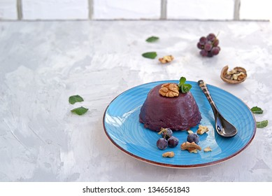 Pelamushi, a Georgian traditional dessert made from grape juice on a blue plate. Decorated with walnuts and berries of frozen grapes. Georgian cuisine.