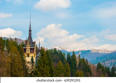 Peles castle clock tower, Sinaia, Romania. Blue sky, white clouds and mountains in the background.