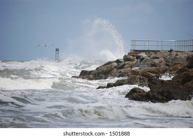 A pelican glides by as breakers crash against the jetty at Ponce Inlet Florida