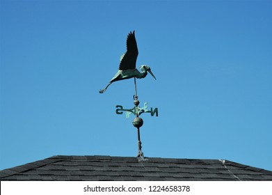 A pelican weathervane atop a roof against a bright blue sky.