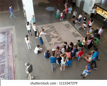 """PELLA, GREECE - MAY 23, 2018: Group of children gather around the """"Hunting a lion""""mosaic reproduction at the Archaeological Museum of Pella."""