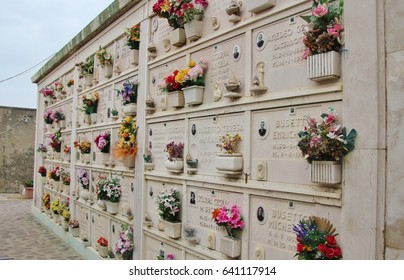 Pellestrina, Italy - April 5, 2017: Columbarium on a small cemetery with pictures of the deceased and colorful artificial flowers. In Pellestrina, on the island Lido di Venezia. Italy, Europe.