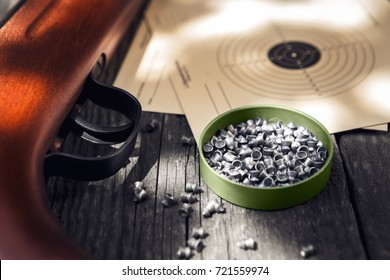 Pellets,air rifle and shooting target on wooden table