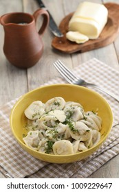 Pelmeni with butter and parsley on a rustic table