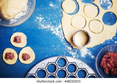 Pelmeni - Russian ravioli. Cooking process with forcemeat on a blue wooden background. Flour is scattered on table. Selective focus.