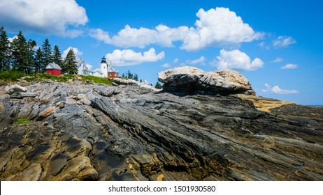 Pemaquid lighthouse, Maine with rocky coastline in foreground and puffy white clouds against blue sky