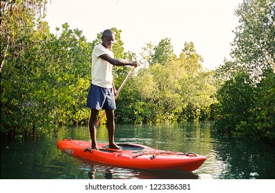 Pemba, Cabo Delgado / Mozambique - October 6th 2018: Man Stand Up Paddle Boarding (SUP) Down A Beautiful River