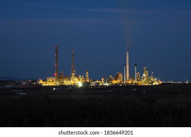 Pembroke oil refinery lit up at night with smoke rising from a chimney stack, Rhoscrowther on the Pembrokeshire coast, near Milford Haven, Wales, UK