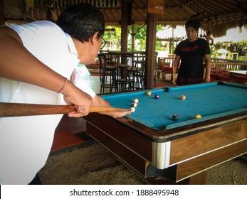 Pemuteran Village, Buleleng, Bali, Indonesia - Jan 02 2021 : Family Holidays Father And Son Playing Billiards At The Bar By The Beach At Pemuteran Village