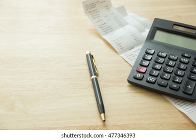 pen, bills under calculator on wood table, natural day light, selective focus, space for copy